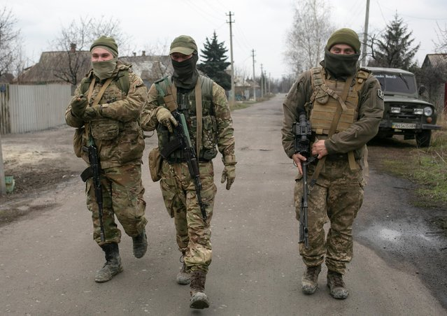 Service members of the Ukrainian armed forces walk along a street in the town of Marinka in Donetsk Region, Ukraine on April 14, 2021. (Photo by Anastasia Vlasova/Reuters)
