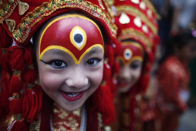 A young Nepalese girl dressed as a Kumari or living Goddess, smiles for camera as she waits for Kumari puja at Hanuman Dhoka, Basantapur Durbar Square in Katmandu, Nepal, Tuesday, Sept 17, 2013. More than hundred girls under the age of nine gathered for Kumari puja, a tradition of worshiping young pre-pubescent girls as manifestations of the divine female energy. The ritual holds a strong religious significance in Newar community. It is a community affair held primarily to save small girls from diseases and bad luck in the years to come. (AP Photo/Niranjan Shrestha)