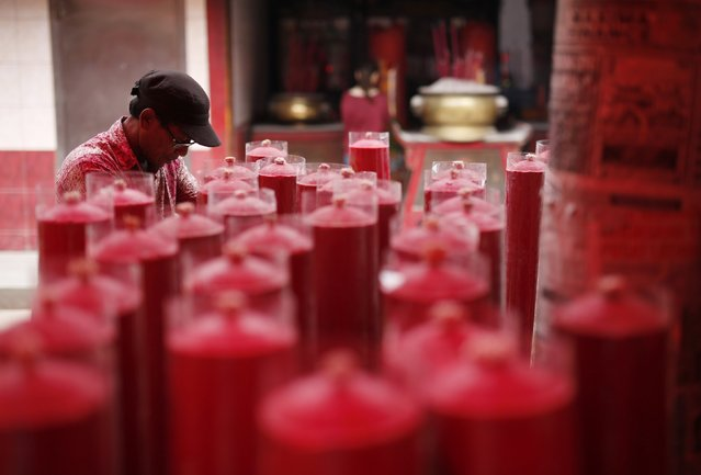 A worker organises large candles at Petak Sembilan Chinese Buddhist temple on the eve of Chinese Lunar New Year celebrations in Jakarta, February 18, 2015. (Photo by Darren Whiteside/Reuters)