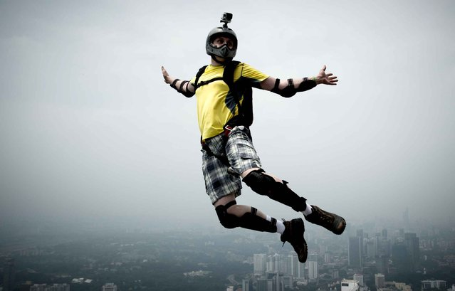 Base jumper Sergey Yunishev of Russia leaps from the 300-metres Open Deck of Malaysia's landmark Kuala Lumpur Tower during the International Tower Jump in Kuala Lumpur on September 27, 2013. (Photo by Mohd Rasfan/AFP Photo)
