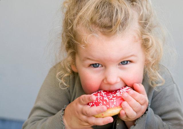 Little girl eating jelly-glazed donut with sprinkles. (Photo by Lisa Valder/Getty Images)
