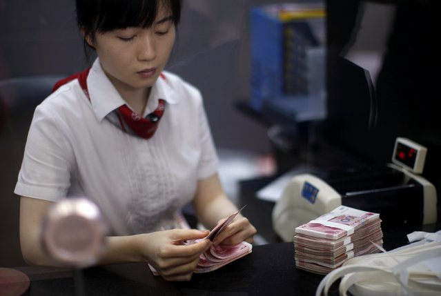 An employee of the Industrial and Commercial Bank of China Ltd (ICBC) counts money at one of the bank's branches at the Shanghai Free Trade Zone in Pudong district, in Shanghai, in this September 24, 2014 file photo. (Photo by Carlos Barria/Reuters)