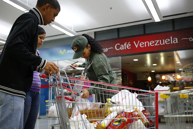 An army reservist checks a list of items purchased as people leave with their shopping at a state-run Bicentenario supermarket in Caracas, May 2, 2014. (Photo by Jorge Silva/Reuters)