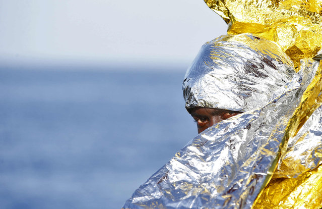A migrant waits to disembark from the rescue vessel Responder, a rescue boat run by the Malta-based NGO Migrant Offshore Aid Station (MOAS) and the Italian Red Cross (CRI), in the Italian harbour of Vibo Marina, Italy, October 22, 2016. (Photo by Yara Nardi/Reuters/Italian Red Cross press office)