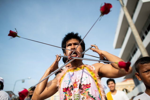 A devotee of the Loem Hu Thai Su shrine has a metal rods with roses pierced through his cheeks as he parades during the annual Vegetarian Festival in Phuket on October 12, 2018. The festival begins on the first evening of the ninth lunar month and lasts for nine days, with many religious devotees slashing themselves with swords, piercing their cheeks with sharp objects and committing other painful acts to purify themselves, taking on the sins of the community. (Photo by Jewel Samad/AFP Photo)