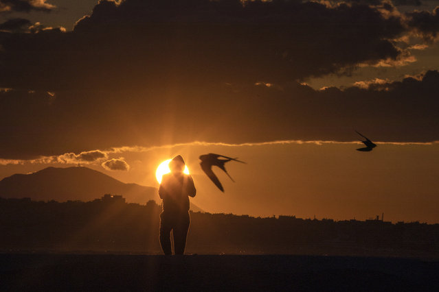 Birds fly as a man walks during a sunset in Alimos, a seaside suburb of Athens, on Tuesday, April 20, 2021. (Photo by Petros Giannakouris/AP Photo)