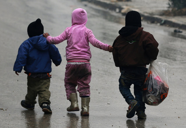 Children walk together as they flee deeper into the remaining rebel-held areas of Aleppo, Syria December 13, 2016. (Photo by Abdalrhman Ismail/Reuters)