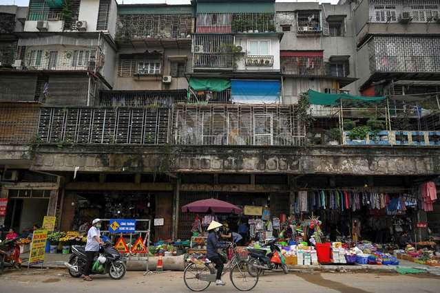 A woman rides her bicycle past shops beneath a residential building in Hanoi on March 31, 2021. (Photo by Manan Vatsyayana/AFP Photo)