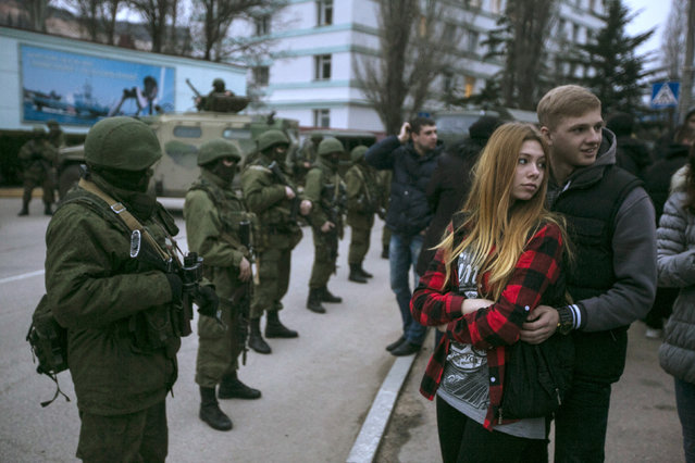 A couple stands next to armed servicemen outside a Ukrainian border guard post in Balaclava March 1, 2014. (Photo by Baz Ratner/Reuters)