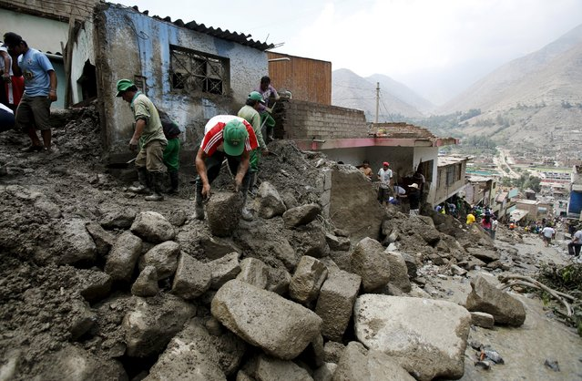 People remove mud and rocks after a massive landslide in Chosica, March 24, 2015. (Photo by Mariana Bazo/Reuters)