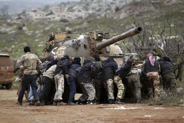Fighters from the Suqour al-Sham Brigade, which is part of the Free Syrian Army, take cover from snipers behind a tank during what activists said were clashes with forces of Syria's President Bashar al-Assad, in the al-Arbaeen mountain area of western Idlib January 30, 2015. (Photo by Khalil Ashawi/Reuters)