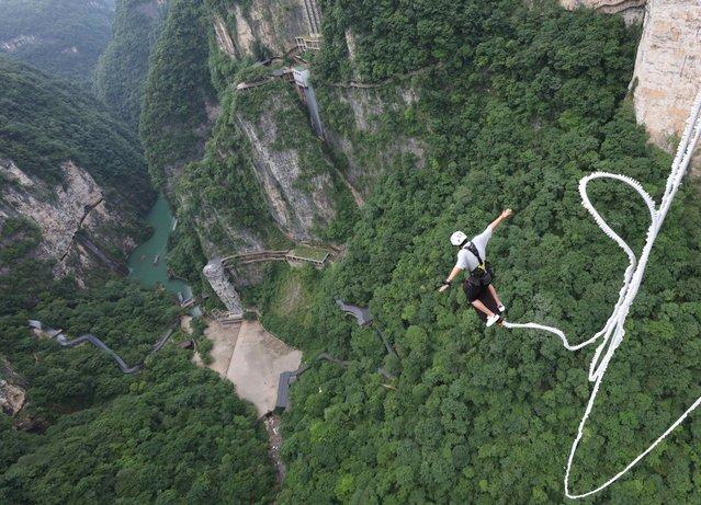 A tourist experiences bungee jumping at the Zhangjiajie Grand Canyon scenic area on July 12, 2021 in Zhangjiajie, Hunan Province of China. (Photo by Wu Yongbing/VCG via Getty Images)