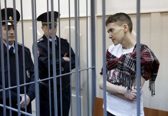 Ukrainian military pilot Nadezhda Savchenko looks out from a defendants' cage as she attends a hearing at the Basmanny district court in Moscow March 26, 2015. Savchenko, 33, was captured by pro-Russian forces and handed over eight months ago to Russia, where she was imprisoned on charges of aiding the killing of two Russian journalists in east Ukraine. At home, she has become a symbol of resistance to Russian aggression. (Photo by Maxim Shemetov/Reuters)