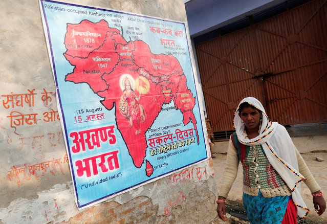 A woman walks past a poster pasted on a wall outside the house of Yogesh Raj, a Hindu activist, in Nayabans village in Bulandshahr district, Uttar Pradesh, India December 5, 2018. (Photo by Adnan Abidi/Reuters)
