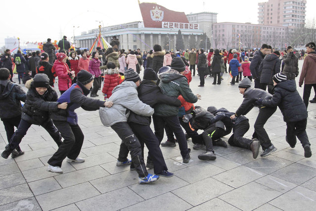"""North Korean boys play """"catch the tail"""" as they gather at Kim Il Sung Square for Lunar New Year in Pyongyang, North Korea, Monday, February 8, 2016. North Korea's state media triumphantly announced in a special news bulletin to the nation on Sunday, February 7, 2016, it had successfully launched a satellite into orbit, calling it a major milestone in the nation's history and the """"greatest gift of loyalty"""" to the country's leader, Kim Jong Un. (Photo by Jon Chol Jin/AP Photo)"""