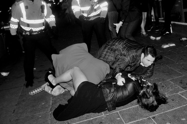 Police look on as a man tries to break up brawling women in Queen Street. (Photo by Brian Anderson)
