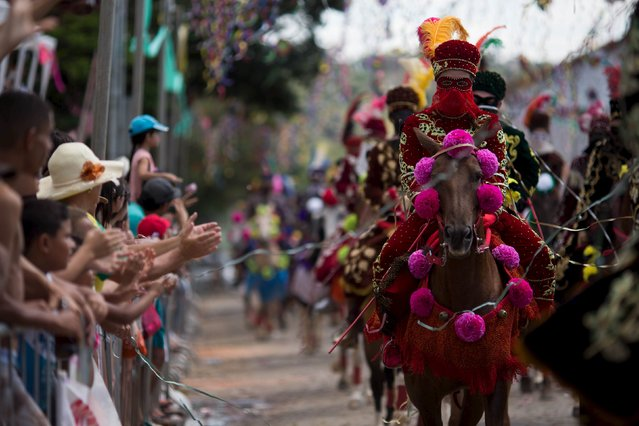 People applaud as revellers participate in the traditional Carnival on horseback, a tradition dating back to the 18th century, in Bonfim, Brazil, February 8, 2016. (Photo by Roosevelt Cassio/Reuters)