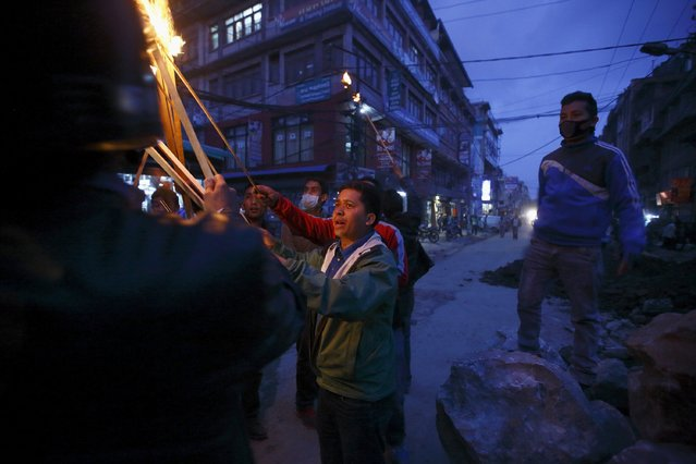 A protester lights a torch as he takes part during the torch rally in Kathmandu April 6, 2015. (Photo by Navesh Chitrakar/Reuters)