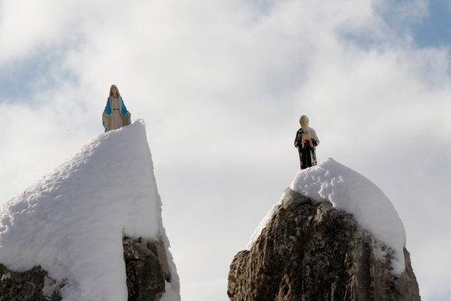 Statues of the Virgin Mary and Saint Charbel are pictured on snow-covered rocks in Zaarour, in the Mount Lebanon Governorate January 11, 2017. (Photo by Mohamed Azakir/Reuters)