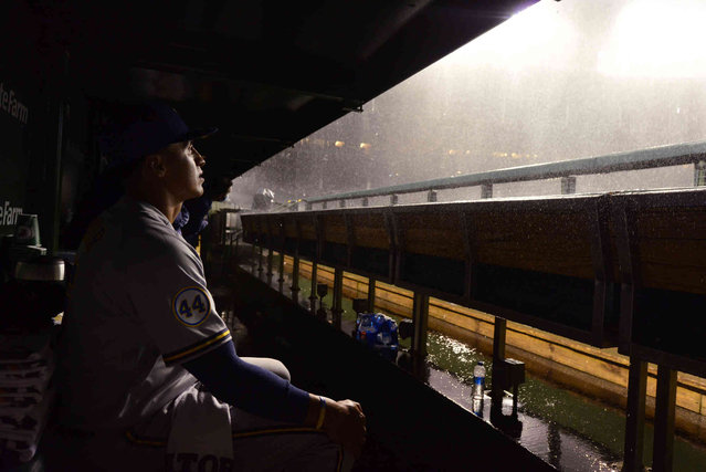 Milwaukee Brewers' Tyrone Taylor sits in the dugout, waiting out a thunderstorm during a rain delay in the team's baseball game against the Chicago Cubs on Tuesday, August 10, 2021, in Chicago. (Photo by Paul Beaty/AP Photo)