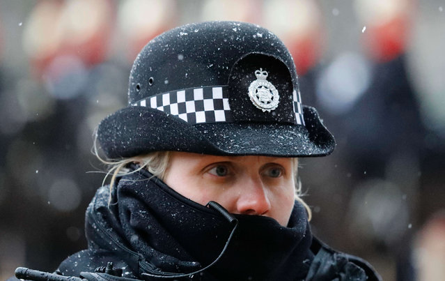 A Metropolitan police woman wrapped up against the cold, watches members of the public, as a section of the Household Cavalry wait for the changing of the guard on Horse Guards parade as snow falls in London, Friday, January 13, 2017. London and the southeast of England were hit by a snow storm Thursday evening and more snow was forecast for Friday. (Photo by Frank Augstein/AP Photo)