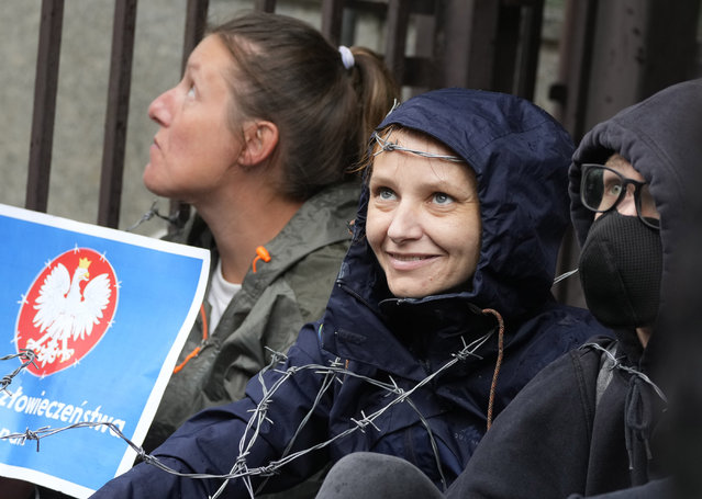 Protesters chained themselves to the fence surrounding the headquarters of Poland's Border Guards and put barbed wire on top of the fence to protest the government's refusal to let in a group of illegal migrants who have been stuck in the open air at the border with Belarus for two weeks, in Warsaw, Poland, Monday, August 23, 2021.(Photo by Czarek Sokolowski/AP Photo)