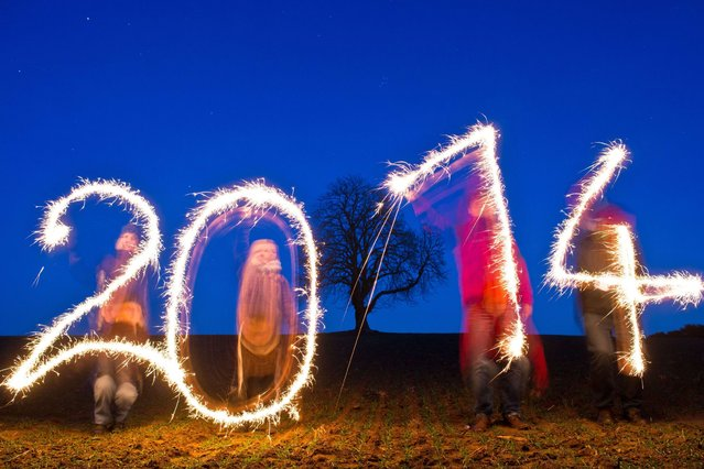 """Four persons posing for the photographer use sparklers as they write the year date """"2014"""" in the air on a field near Jacobsdorf, northeastern Germany, on December 21, 2013 (picture taken with long exposure time). (Photo by Patrick Pleul/AFP Photo/DPA)"""