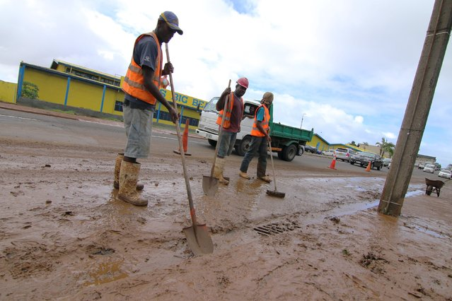 Suva City Council workers clean up mud from Grantham Road in the Raiwaqa suburb of Fiji's capital Suva, as a cleanup continues in the wake of Cyclone Winston, February 22, 2016. (Photo by Steven Saphore/Reuters)