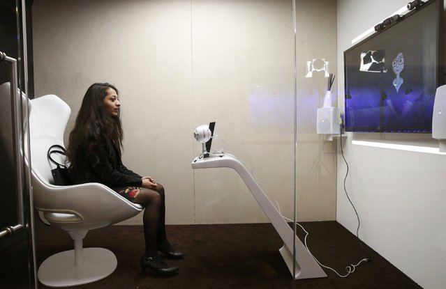 An attendee communicate with SARA, a socially aware robot assisstant, during a presentation at the annual meeting of the World Economic Forum (WEF) in Davos, Switzerland, January 17, 2017. (Photo by Ruben Sprich/Reuters)
