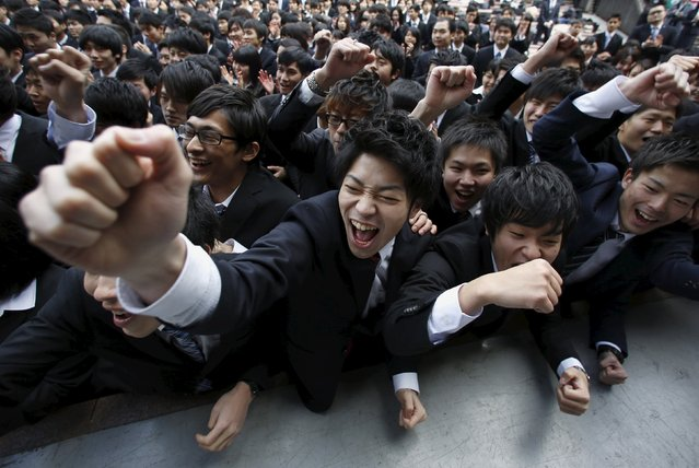 Japanese college students shout and raise their fists during a pep rally held to boost their morale ahead of their job hunt, at an outdoor theatre in Tokyo February 25, 2016. (Photo by Issei Kato/Reuters)
