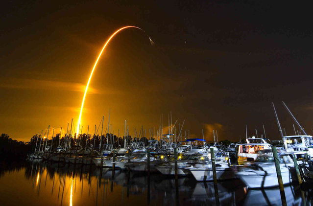 This long exposure photo shows the launch of a SpaceX Falcon 9 rocket on a resupply mission for NASA to the International Space Station from Pad 39A at Kennedy Space Center, seen from Merritt Island, Fla., Sunday, August 29, 2021. The SpaceX shipment of ants, avocados and a human-sized robotic arm rocketed toward the International Space Station on Sunday. (Photo by Malcolm Denemark/Florida Today via AP Photo)