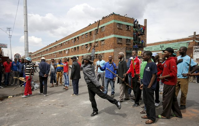 Locals gesture outside a hostel during anti-immigrant related violence in Johannesburg, April 17, 2015. (Photo by Siphiwe Sibeko/Reuters)