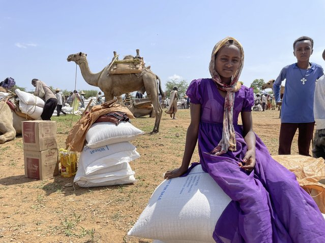 A young Tigrayan girl sits on sacks of wheat after the World Food Programme (WFP) distributed food to around 13,000 people in the rural village of Zelazle in the Tigray region of northern Ethiopia Monday, August 23, 2021. (Photo by Claire Nevill/WFP via AP Photo)