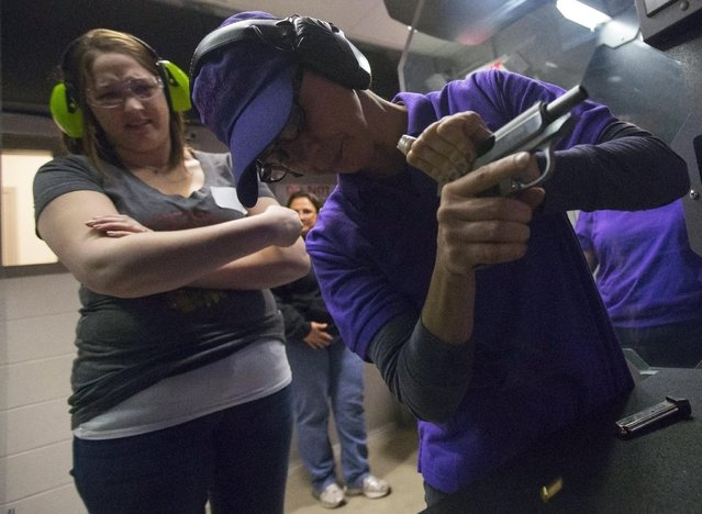 Instructor Dawn Waters (R) helps Alyssa Keehr with a jammed gun during a meeting of The Well Armed Woman Shooting Chapters at GAT Guns in East Dundee, Illinois, April 21, 2015. (Photo by Jim Young/Reuters)