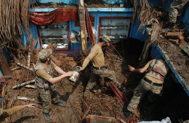 Pakistani soldiers remove belongings from a home after it was damaged in heavy rain and winds in Peshawar on April 27, 2015. (Photo by A. Majeed/AFP Photo)