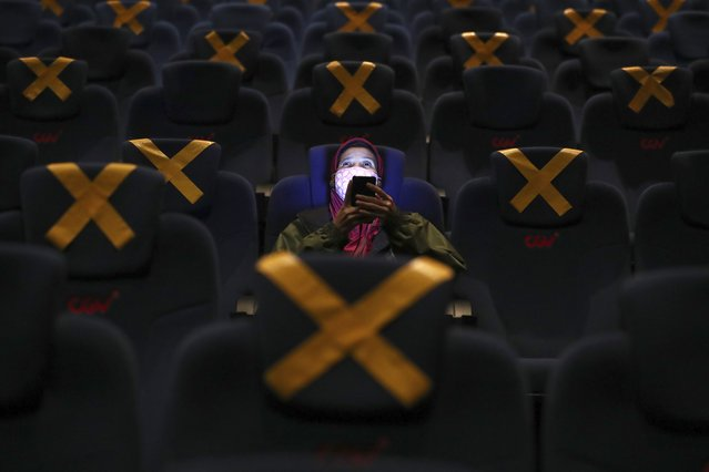 A customer uses her mobile phone before the start of a movie show as she sits amid physical distancing markers during the first day of reopening at a cinema in Jakarta, Indonesia, Thursday, September 16, 2021. Cinemas in several cities shut during the deadly wave of coronavirus outbreak that hit the country in July were allowed to begin reopening with capacity limit as cases decline. (Photo by Tatan Syuflana/AP Photo)