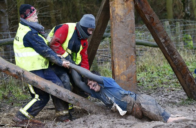 A competitor is dragged out of the mud during the Tough Guy event in Perton, central England, January 26, 2014. (Photo by Darren Staples/Reuters)