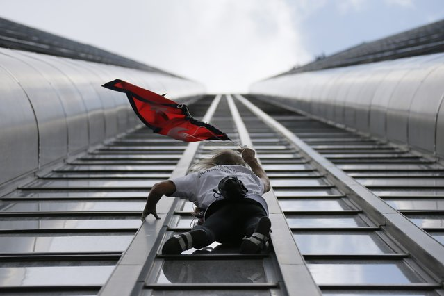 "French climber Alain Robert, also known as ""Spiderman"", holds the flag of Nepal as he scales the Tour Montparnasse, a 210-metre (689 ft) building in central Paris, France April 28, 2015, to show support for the victims after the earthquake in Nepal. (Photo by Gonzalo Fuentes/Reuters)"