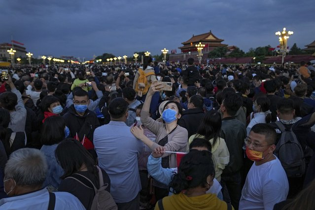 A woman wearing a face mask to help protect from the coronavirus takes a smartphone selfie with the crowds on a street near Tiananmen Square as they watch a flag raising ceremony on the National Day in Beijing, Friday, October 1. (Photo by Andy Wong/AP Photo)