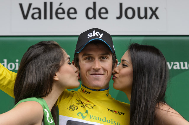 British Geraint Thomas of Team Sky Procycling, the new overall leader, is kissed by two hostess on the podium with the yellow jersey after the first stage, a 19,2 km team race against the clock, between La Vallee de Joux and Juraparc at the 69th Tour de Romandie UCI ProTour cycling race, in Vallorbe, Switzerland, Tuesday, April 28, 2015. (Photo by Jean-Christophe Bott/Keystone via AP Photo)