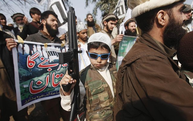 The son of a supporter of the Jamaat-ud-Dawa Islamic organization holds a toy gun at a rally to mark Kashmir Solidarity Day in Peshawar, Pakistan, on February 5, 2014. (Photo by Fayaz Aziz/Reuters)