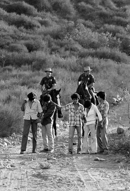 U.S. Border Patrolmen Ed Pyeatt, right, ands Steve Shields, left, march  five illegal aliens to the holding center shortly after their apprehension in the desert, August 18, 1981. (Photo by Lennox McLendon/AP Photo)