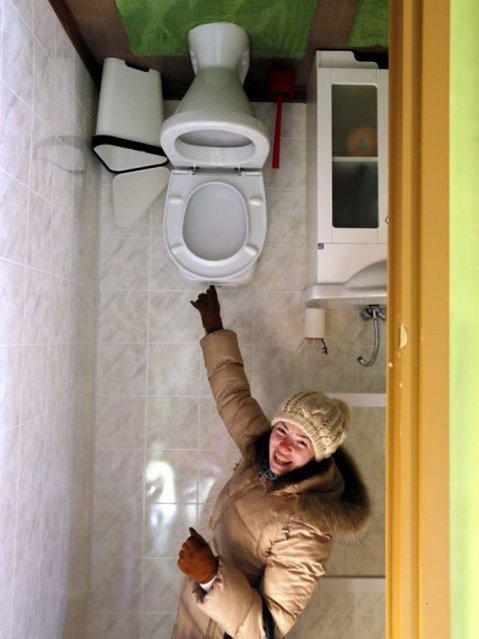 "A visitor explores a bathroom in the ""Upside Down House"". (Photo by Yuri Kochetkov/EPA)"