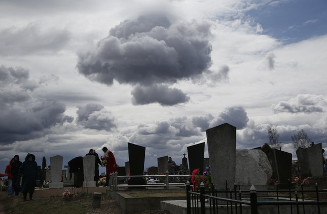 Belarusians stand near the graves of their relatives, during an Orthodox Christian tradition, in a cemetery in the town of Novogrudok, 150 kms,  93 miles, west of Minsk, Belarus, Tuesday, April 21, 2015. (Photo by Sergei Grits/AP Photo)