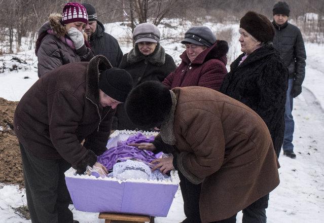 Relatives of Elena Volkova, a victim of shelling, grieve at her funeral in Avdiivka, eastern Ukraine, Monday, February 6, 2017. (Photo by Evgeniy Maloletka/AP Photo)