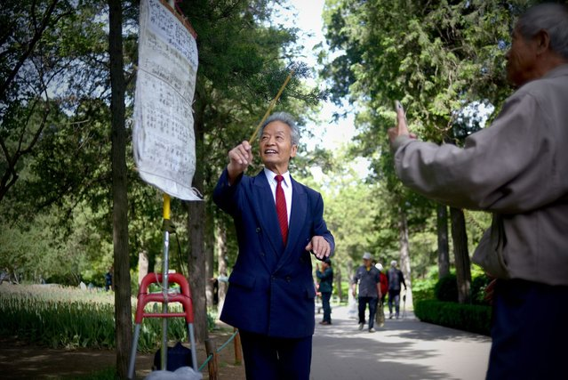 An elderly man (C) practices singing at a park in Beijing on May 3, 2015. (Photo by Wang Zhao/AFP Photo)