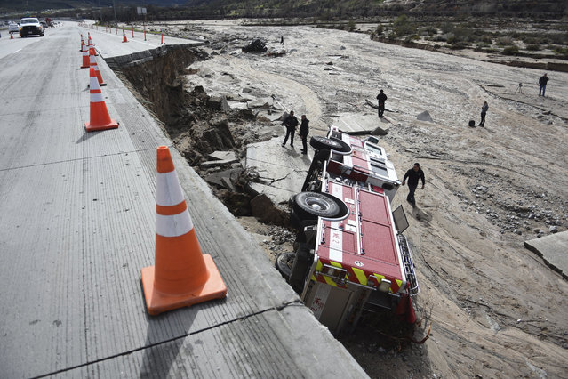 Officials look over the scene where a San Bernardino County Fire Department fire engine fell Friday from southbound Interstate 15 where part of the freeway collapsed due to heavy rain in the Cajon Pass, Calif., Saturday, February 18, 2017. A huge Pacific storm that parked itself over Southern California and unloaded, ravaging roads, opening sinkholes  eased off Saturday but it was only a temporary reprieve as new storms took aim farther north. (Photo by David Pardo/The Daily Press via AP Photo)