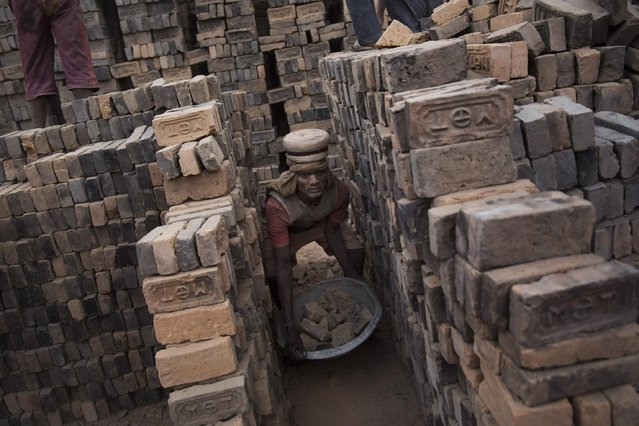 In this Wednesday, May 13, 2015 photo, an indian laborer works at a brick factory in Bhaktapur, Nepal. (Photo by Bernat Amangue/AP Photo)