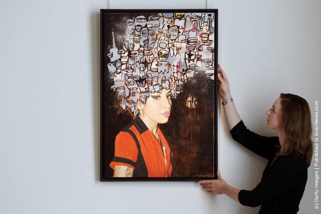 A Bonhams intern stands beside a work entitled 'Amy' by Cyclops