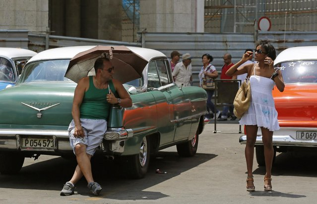 A taxi driver shades himself with an umbrella as he watches a woman prepare to cross the street near Central Park in downtown in Havana, Cuba, Saturday, May 16, 2015. The private cabbie rests on his 1956 Cadillac Sedan De Ville as he waits for customers. He said he tends to work with tourists who need a driver for the entire day, for which he charges $50 dollars. (Photo by Desmond Boylan/AP Photo)